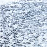 Cobblestone sidewalk covered with ice and snow