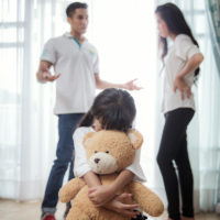 parents arguing in front of daughter who buries herself in stuffed bear