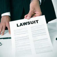 lawyer passes lawsuit document to camera