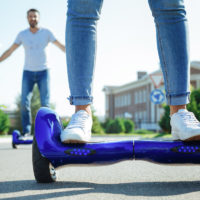 Man and woman riding hoverboard down the street