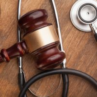 Stethoscope and gavel on courtroom table.