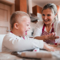 A laughing down syndrome child with his mother indoors baking.