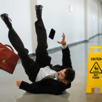 Businessman falls on slippery floor