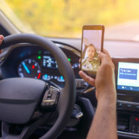 Male driver using smartphone to to take selfie while driving