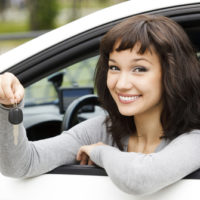 Young female in car holding her car keys