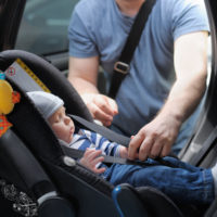 Father straping baby in car seat