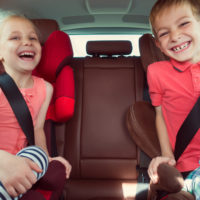 Two kids wearing seat belts