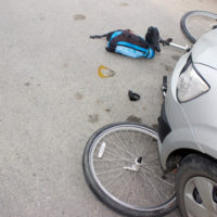 Grey car runs over bike