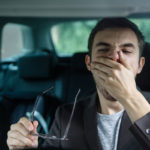 drowsy driver yawning with hand to mouth