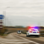 Police car chasing the offender at high speed on the highway .