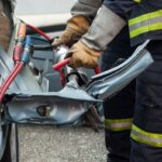 closeup of french rescue man with pneumatic machine on crashed car